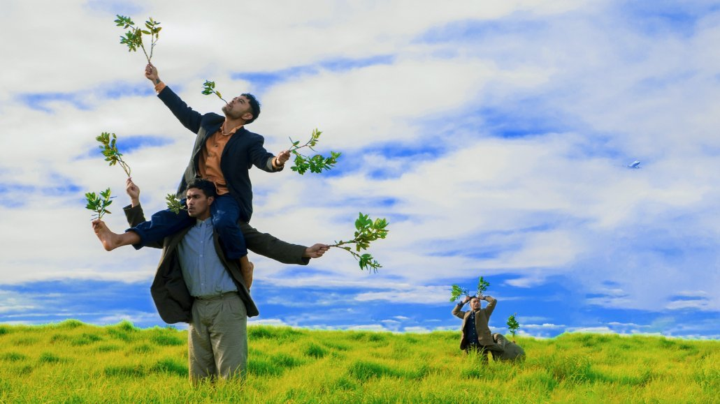 Dancers in a green field holding twigs as cigarettes
