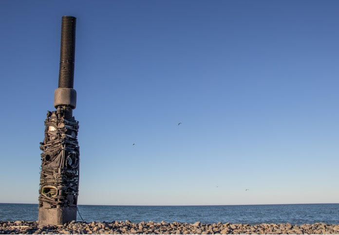 Black stack sculpture by Susan Mabin on the beach.