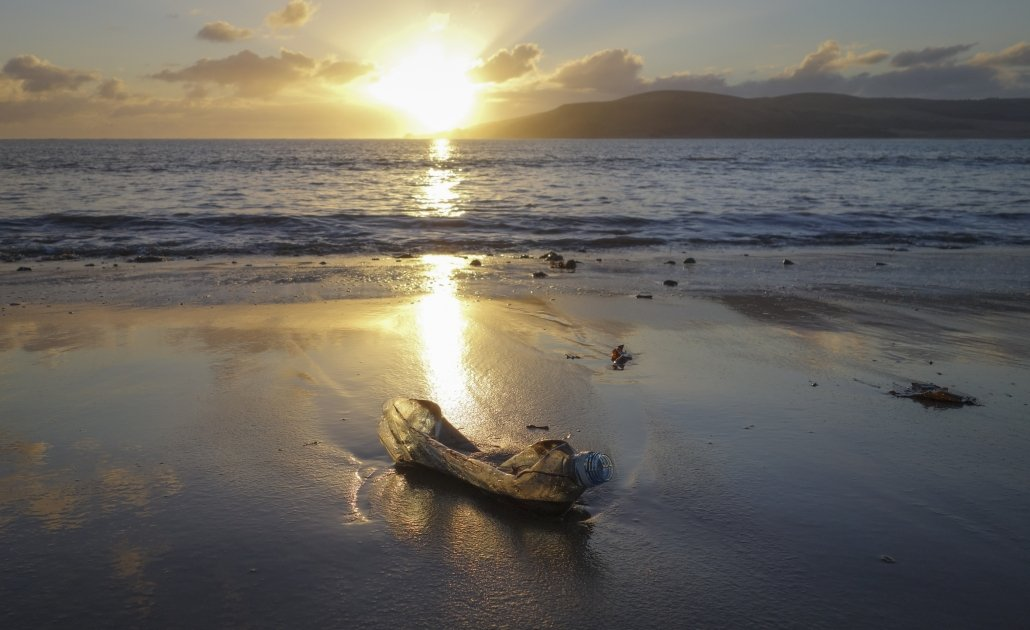 Washed up plastic bottle on the beach with sun setting over Kapiti Island