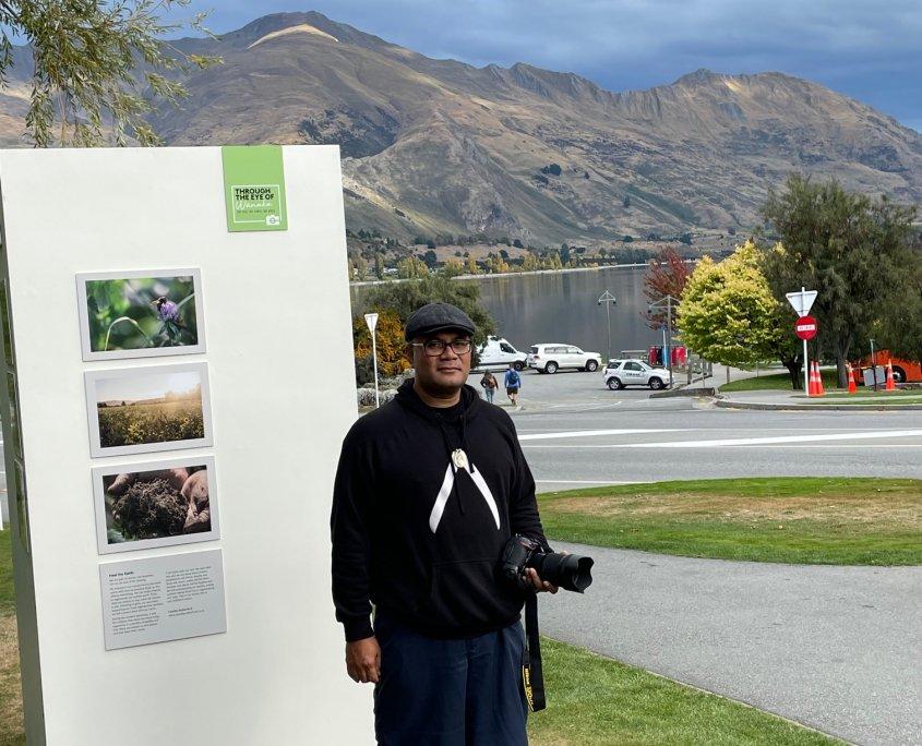 Raymond Sagapolutele standing beside Through the Eye of Wānaka outdoor exhibition