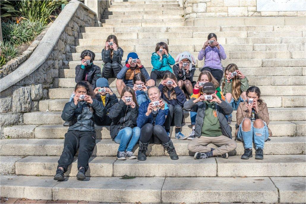 Group of young students exploring storytelling using a camera lens. Image credit Raymond Sagapolutele